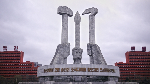 "The iconic North Korea Worker's Party Monument in Pyongyang, DPRK, represents the three pillars of the Revolution: Workers (hammer), Farmers (sickle), and Intellectuals (brush). The slogan says: ""The organizers of the victory of the Korean people and the"
