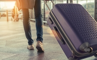Traveler with suitcase in airport (Photo via champlifezy@gmail.com / iStock / Getty Images Plus)